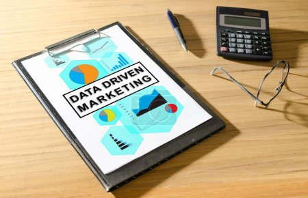 Data driven marketing concept on a clipboard with a calculator