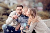 Happy young family making bubbles outdoor