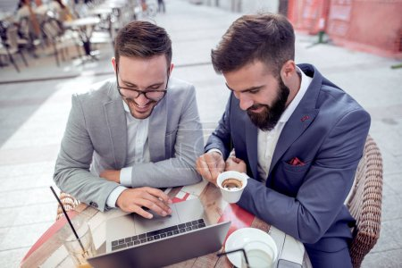 Two businessmen working in cafe on laptop