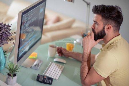 Photo pour Jeune homme travaillant à la maison sur son ordinateur . - image libre de droit