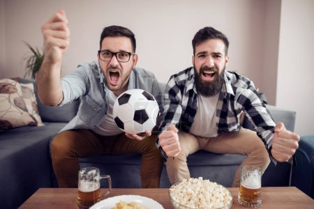 Friendship, sport, people and entertainment concept - happy male friends watching soccer on tv at home.