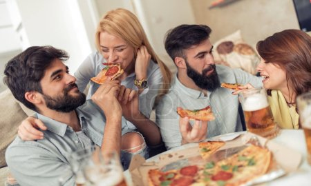 Group of young people eating pizza while having fun together.