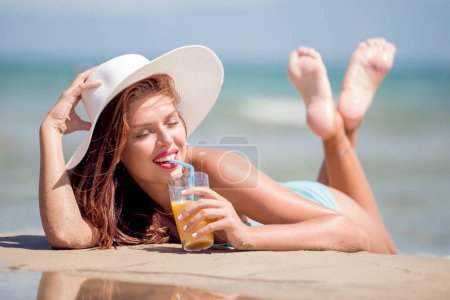 Beautiful woman lying on the beach with cocktail.