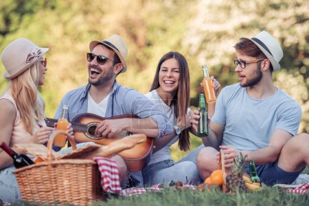 Happy young friends with hats and sunglasses having picnic in park