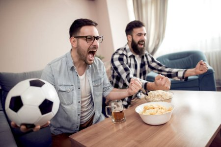 Friendship,sport, people and entertainment concept - happy male friends watching soccer on tv at home.