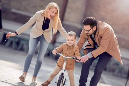 Young father and mather teaching son to ride bicycle in city street.