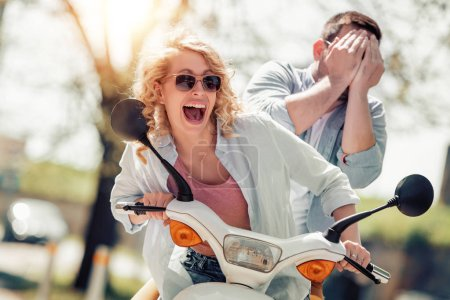 Cheerful couple having fun together on scooter.