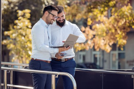 Two businessmen talking about working project outdoor,using a laptop.
