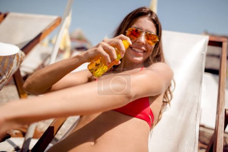 Travel, tourism, summer and people concept - smiling woman on vacation in swimwear sitting in chair and sunbathing on beach.