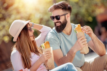 Young couple eating sandwiches outdoors.