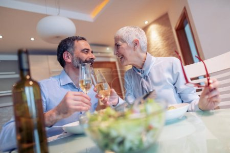 Photo for Beautiful mature couple talking and smiling while having a romantic lunch at home. - Royalty Free Image