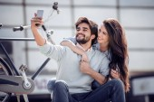 Young couple making selfie on smartphone and sitting on stairs