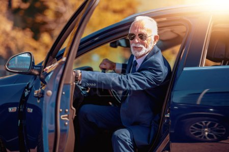side view of confident mature senior businessman in suit getting out of car in daytime