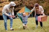 happy family having fun with kite on picnic together in park in daylight