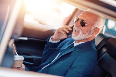 mature senior businessman in suit with mobile phone riding on back seat of car