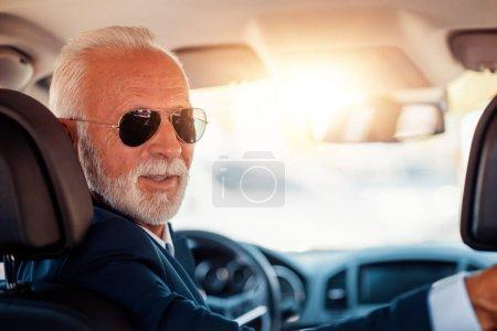 Confident senior businessman driving car