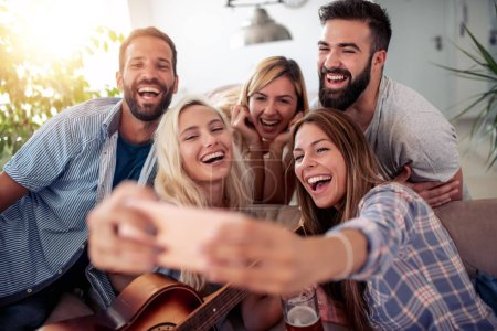 Photo for Friends having party at home,playing guitar and enjoying together. - Royalty Free Image