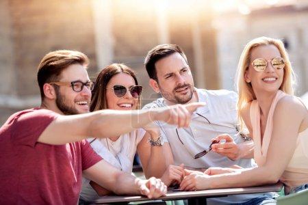 Foto de Grupo de cuatro amigos que se divierten en la cafetería junto. Dos mujeres y dos hombres en el café hablando, riendo y disfrutando de su tiempo. - Imagen libre de derechos