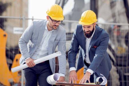 Photo pour Ingénieur heureux discutant avec collègue au chantier de construction sur la journée ensoleillée. - image libre de droit