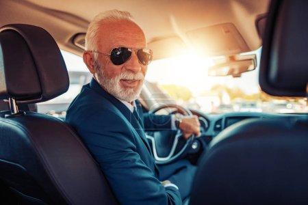 Man in car. Confident senior businessman driving a car.