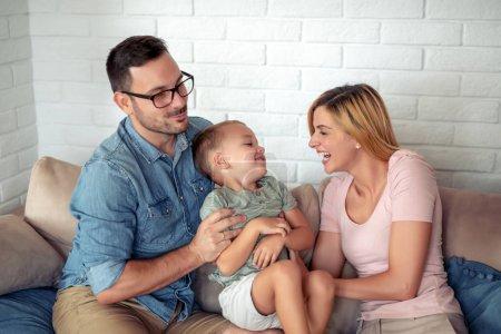 Photo pour Joyeux famille assis sur le canapé riant ensemble. Des parents joyeux jouant avec leur fils à la maison . - image libre de droit