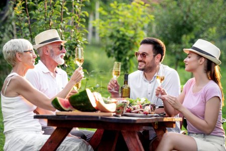 Photo for Family having barbecue lunch in their garden. - Royalty Free Image