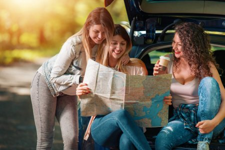 Three young girls going on vacation with car.They ...
