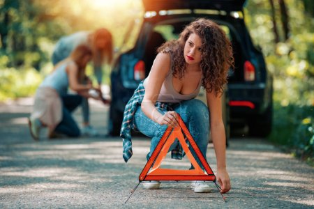 Photo for Girls on the road trying to fix their car.Changing tire on broken car on road. - Royalty Free Image