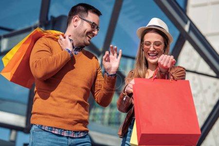 Photo pour Beau jeune couple aimant porter des sacs à provisions et profiter ensemble tout en marchant dans la ville à la journée ensoleillée - image libre de droit