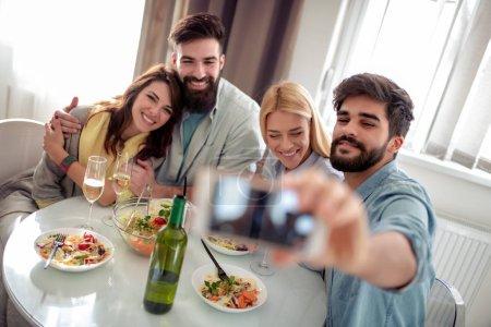 Photo pour Loisirs, manger, manger et boire, personnes et vacances concept-souriant amis déjeuner et boire du vin à la maison . - image libre de droit