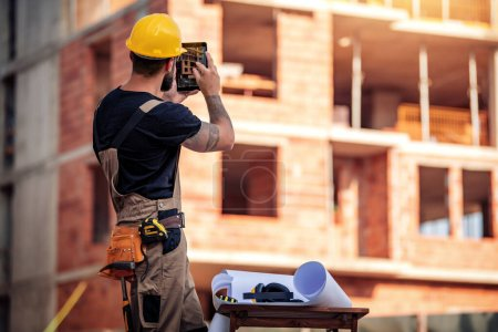 Photo for Business, building, paperwork and people concept-back view of engineer standing on construction site, take picture with tablet. - Royalty Free Image