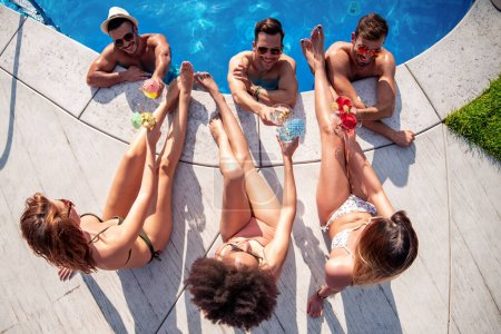 Photo for View from top.Group of young friends have fun in swimming pool, drink cocktails and toast together. - Royalty Free Image