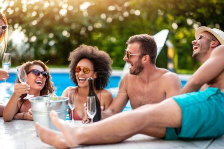 Photo for Happy young friends with wine enjoying in pool party. - Royalty Free Image