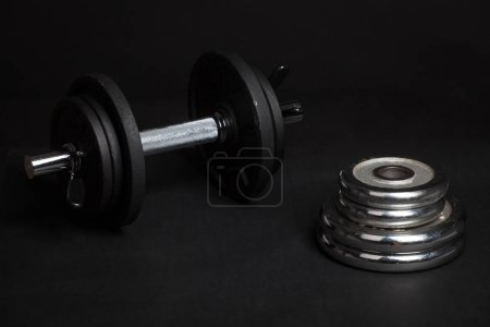 Photo for Dumbbell and barbell discs for workout on black background - Royalty Free Image