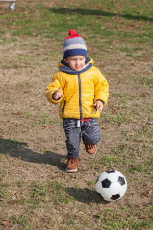 Photo for Little boy playing with soccer or football ball. sports for exercise and activity. - Royalty Free Image