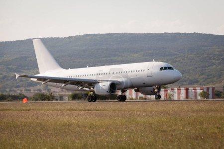 Photo pour L'avion blanc atterrit sur l'aéroport . - image libre de droit