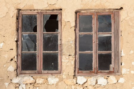 Photo pour Vieilles fenêtres avec des vitres cassées sur le mur d'un vieux bâtiment - image libre de droit