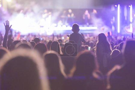 Photo pour Silhouettes de concert se pressent devant les lumières de la scène. Fans lors d'un concert de la vie - image libre de droit