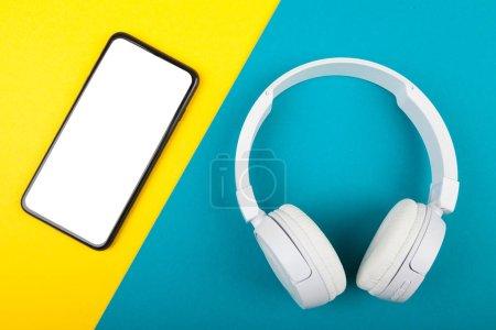 Photo pour Smartphone, téléphone portable avec casque blanc sans fil sur fond bleu et jaune. Prêt à écouter de la musique . - image libre de droit