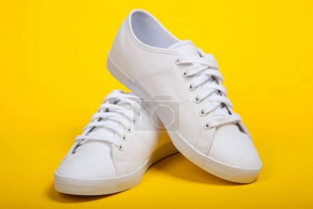 Photo for Pair of new white sneakers on yellow background - Royalty Free Image