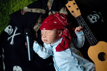 Little baby in a rocker bandana lies with a guitar...