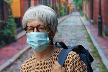 Photo for Portrait of mature woman with grey hair in casual clothes in medical protective mask with backpack on street - Royalty Free Image