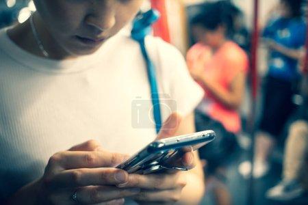 Photo pour Jeune femme utilisant le téléphone mobile en ville - image libre de droit