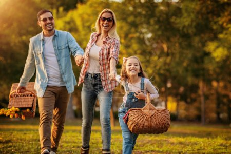 Photo for Happy family having picnic in park.Young happy family of three having fun together.Family fun outside. - Royalty Free Image