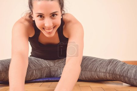 Portrait of sport woman streching legs. Indoors...