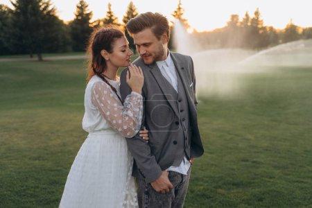 Photo pour Belle femme enceinte en robe blanche avec un bel homme tout en arrosant la pelouse le soir - image libre de droit