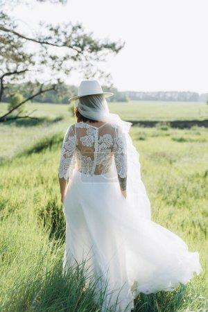 Photo pour Vue arrière de la femme élégante portant chapeau fedora en robe blanche debout dans le domaine - image libre de droit