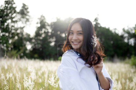 Photo for Asian women happy smile on relaxing time at the meadow and grass - Royalty Free Image