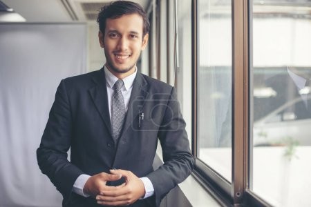 Photo pour Bel homme d'affaires souriant, debout, au pouvoir - image libre de droit