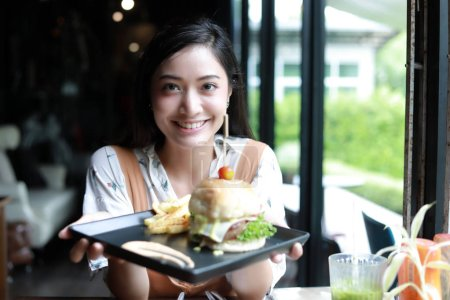 Photo for Asian women smiling and happy and enjoyed eating hamburgers at coffee and restaurant on relax time - Royalty Free Image